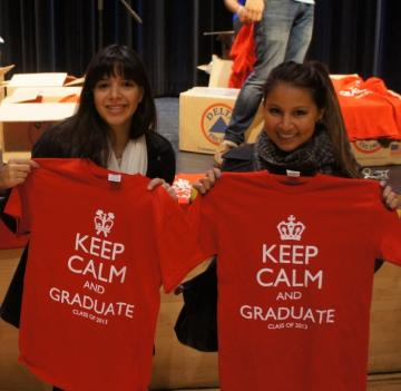 two students holding senior class t-shirts